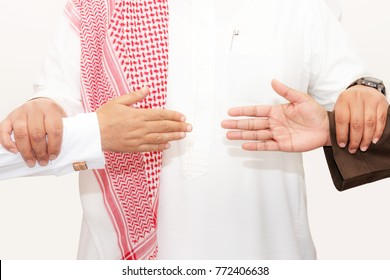 Saudi man holds two hands persons to reconciliation agreement as shake hands concept