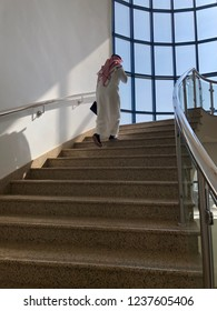 Saudi man wearing traditional clothes climbing up the stairs in the office