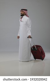 A saudi person traveling and pull out a travel bag on white background   - Shutterstock ID 1932020042