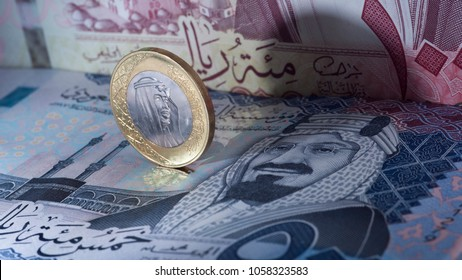 Saudi Riyal Coin Standing on Top of Banknotes
