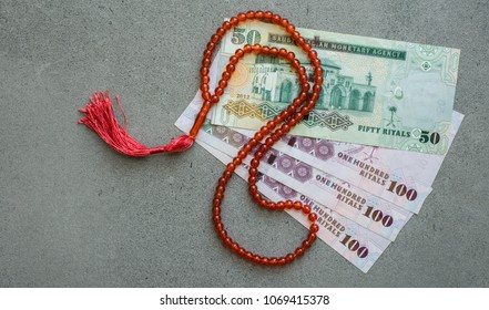 Saudi riyal currency notes with Islamic prayer beads. A concept for Islamic finance and banking.