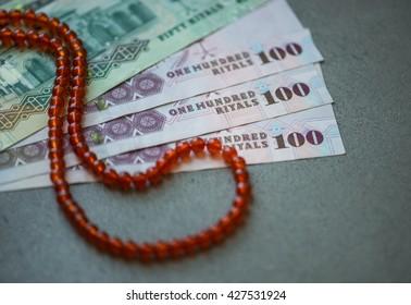 Saudi Riyal currency notes and Islamic prayer beads. Sharia'h or Islamic banking.