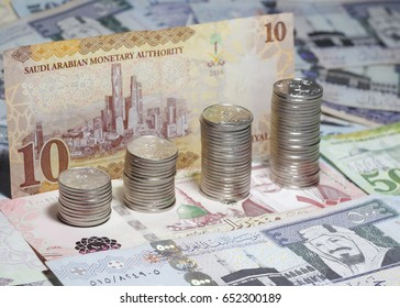 Saudi Riyals bank notes with makkah , medina , riyadh landmarks. Coins designed to show religious tourism supporting financial investment opportunities