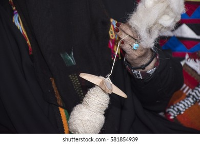 Saudi woman weaving wool, traditional handcrafts from Saudi Arabia, make (a complex story or pattern) from a number of interconnected elements