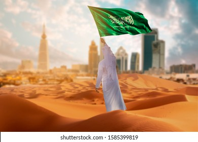 Saudi young Arab man holding Saudi Arabia  flag, celebrating the national day - Shutterstock ID 1585399819