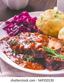 Sauerbraten. German stewed beef meat with red cabbage and potato dumpling