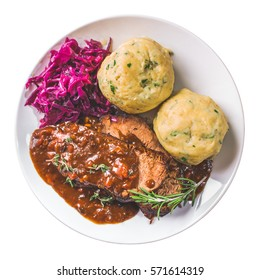 Sauerbraten. German stewed beef meat with red cabbage and potato dumpling. Top view, isolated.
