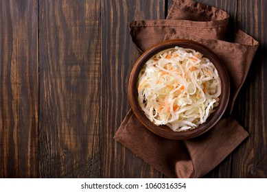 Sauerkraut with carrots in bowl on wooden background with copy space. Marinated vegetables. Vegetarian vegan food. Top view, flat lay