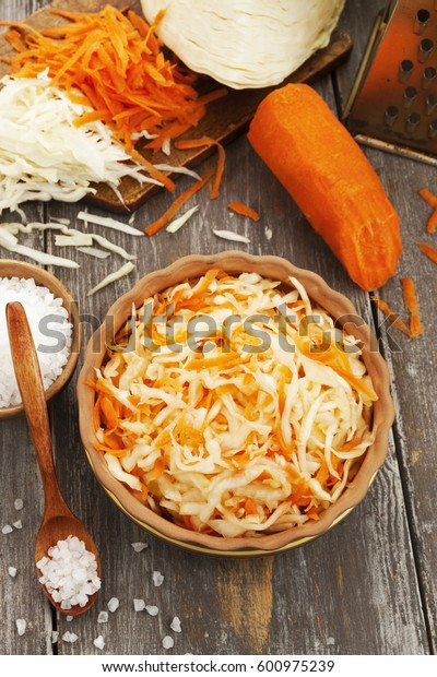 Sauerkraut in the ceramic bowl on the wooden table