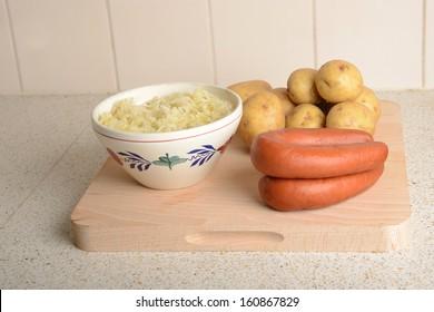 sauerkraut, potatoes and smoked sausage on a wooden shelf