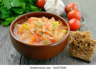 Sauerkraut soup in brown bowl on wooden table