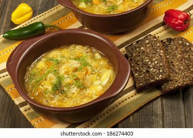 Sauerkraut soup in ceramic  bowl on wooden table