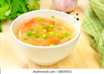 Sauerkraut soup in white bowl on wooden table