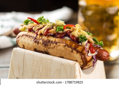 Sauerkraut sweet mustard hot dog and glass of beer on wooden table side view
