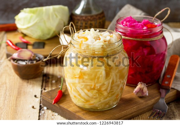 Sauerkraut Sortenschutzgläser. Sauerkraut hausgemacht mit Karotten und Salatkohl mit Rüben auf einem Holztisch. Fermentierte Lebensmittel. Kopiert Platz.