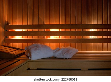 Sauna interior with white bathrobes leaving room for type.