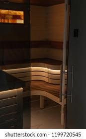 Sauna with open doors and luxury interior. Sauna with open doors and wooden seats with lights. Modern sauna interior. Sauna room with lights.
