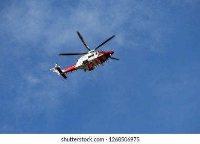 SAUNDERSFOOT, PEMBROKESHIRE, WALES - AUGUST 2018: Helicopter of the HM Coastguard air-sea rescue service in flight against a depp blue sky.