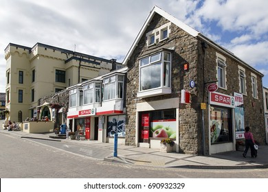 Saundersfoot, UK: July 05, 2016: A local Spar shop. A woman walks by and people sit outside a pub. These little village shops are very convenient for shopping essentials.