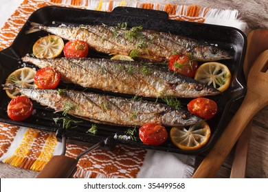 saury grilled with lemon and tomato on a grill pan on a table close-up. horizontal