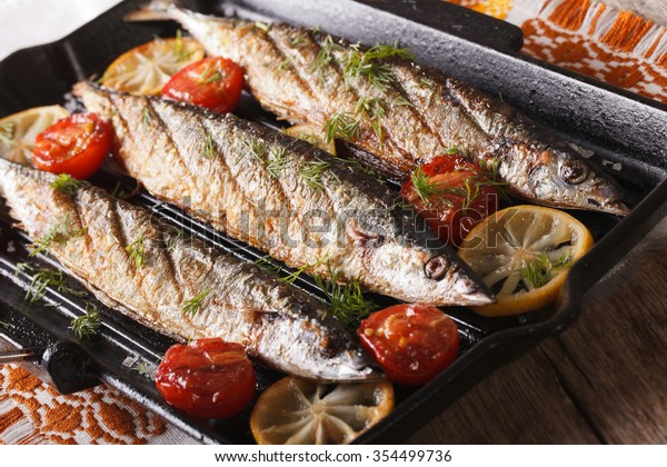 saury grilled with vegetables on the grill pan on the table closeup. horizontal