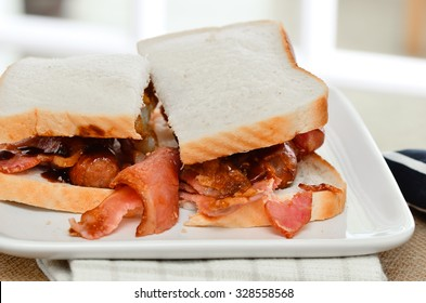 Sausage and bacon sarnie with brown sauce on white bread.