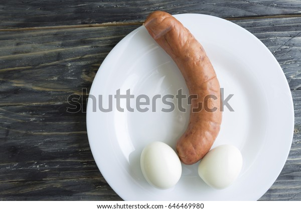 Sausage and chicken eggs on a white plate