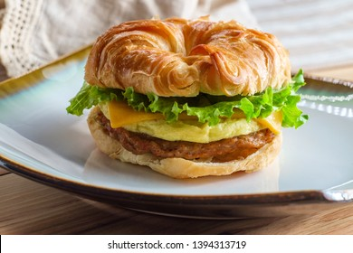 Sausage egg and cheese on flaky French croissant roll with romaine lettuce