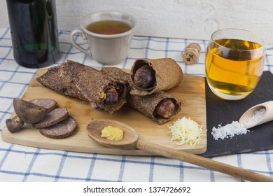 Sausage galette. Traditional Breton speciality sausage pancake, with cheese, andouille at served with a blue and white checkered tablecloth.