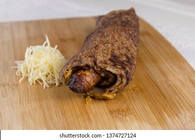 Sausage galette. Traditional Breton speciality sausage pancake, with cheese at served on a wood board.