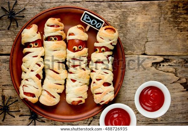 Momies de saucisses dans une pâte effrayante fête de célébration d'halloween avec des yeux drôles sur fond vintage bois