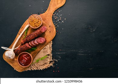 Sausage paperoni. Salami with paprika. On a black wooden background. Top view. Free space for your text.