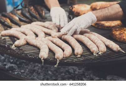 Sausage party. Chef cooking at barbecue big grill outdoors. Cookout bbq food. Roasted pork bratwurst german sausages, white polish kielbasa. Meat grilled meal. Street fast food.
