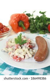 sausage with pasta salad against white background
