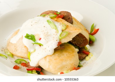 Sausage and perogies, with red pepper, green onion, and sour cream on white background
