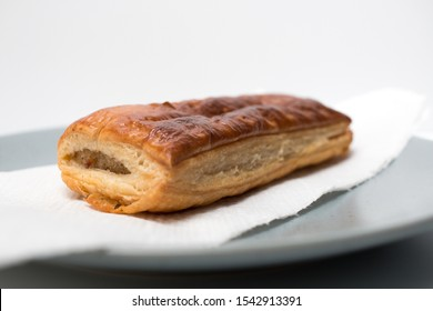 A sausage roll just out of the oven on a plate from the front side on a white background. Dutch Saucijzenbroodje.