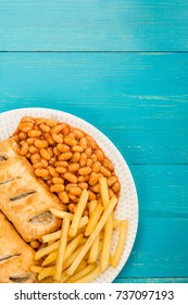 Sausage Rolls With Baked Beans Chips And French Fries On A Blue Background With Copy Space