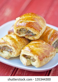 Sausage rolls on a plate on a wooden table