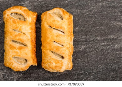 Sausage Rolls in Pastry On A Black Slate Kitchen Tile With Copy Space