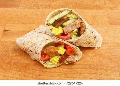 Sausage and salad sandwich wraps on a wooden chopping board