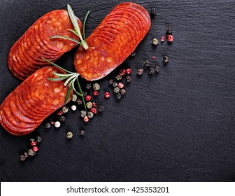 sausage or salami with fresh herbs colorful seasoning on black stone