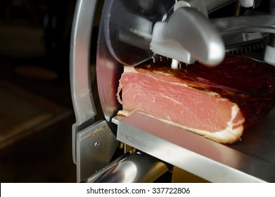 A sausage slicer with a big piece of ham