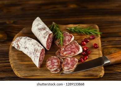 Sausage slices with greens and kernels of pomegranate on a beautiful wooden background close up