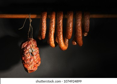 Sausage smoked with smoke. A composition of smoked cold cuts on a black background.