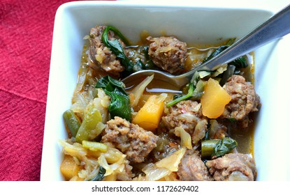 Sausage soup with Italian sausages, rutabaga, green beans, cabbage and spinach: close up, selective focus