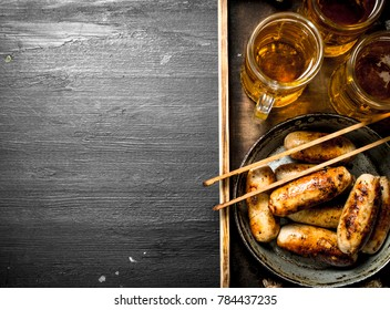 Sausages with beer on a wooden tray. On the black chalkboard.