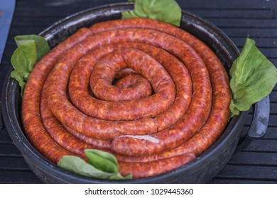 sausages in a cooker with green salad, shallow focus