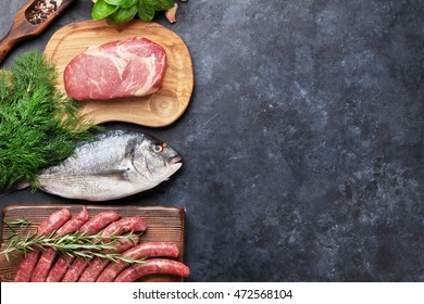Sausages, fish, meat and ingredients cooking. Top view with copy space on stone table