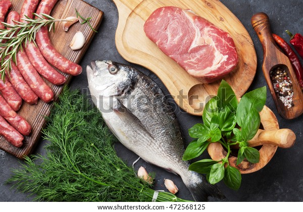 Sausages, fish, meat and ingredients cooking. Top view on stone table