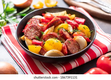 Sausages fried with peppers, tomatoes, and onions in a black plate on a dark background close-up. Sausages stewed with vegetables. Traditional Hungarian food lecho.